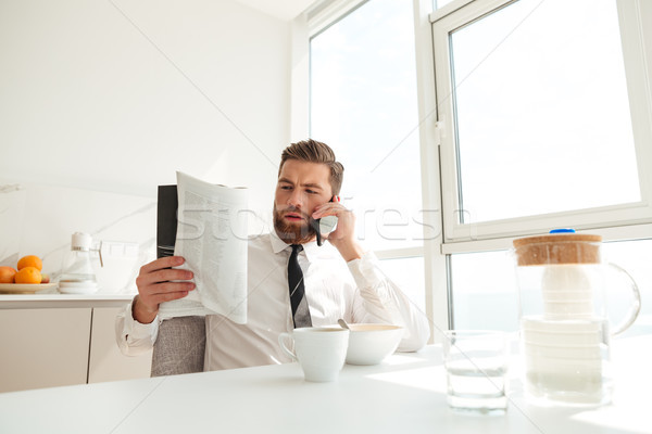 Serious bearded business man reading journal Stock photo © deandrobot
