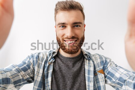 Smiling bearded man in checkered shirt making selfie Stock photo © deandrobot