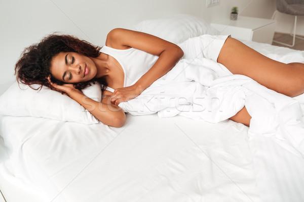 Fiatal higgadt nő pizsama alszik ágy Stock fotó © deandrobot