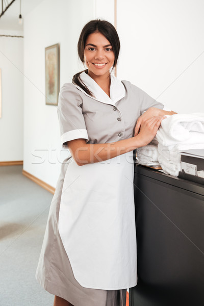 Smiling housekeeping worker standing with bedclothes linen in cart Stock photo © deandrobot