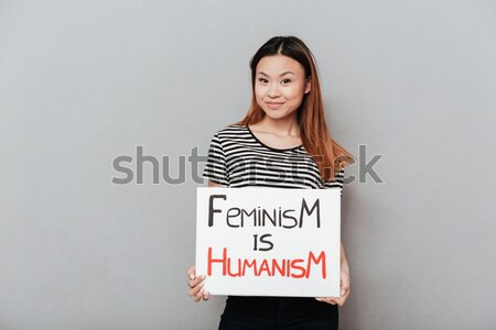 Attractive young caucasian lady holding blank with text about feminism. Stock photo © deandrobot