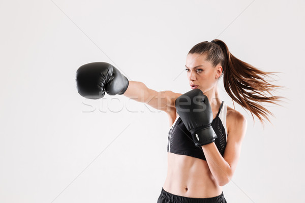 Portrait of a young motivated woman doing boxing Stock photo © deandrobot