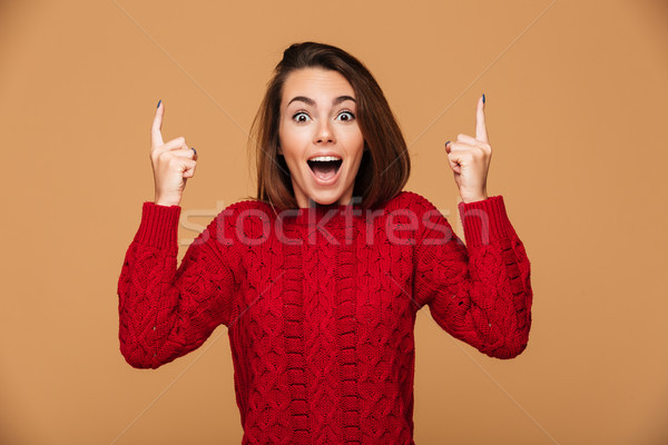 Happy exited young woman in red sweater pointing up with two fin Stock photo © deandrobot