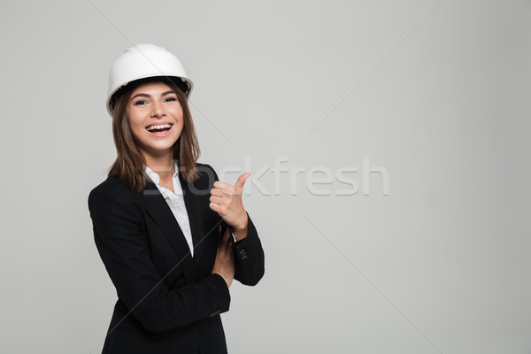 Portrait of a cheerful pretty woman in hard hat and suit Stock photo © deandrobot