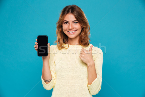 Smiling woman in sweater showing blank smartphone screen Stock photo © deandrobot