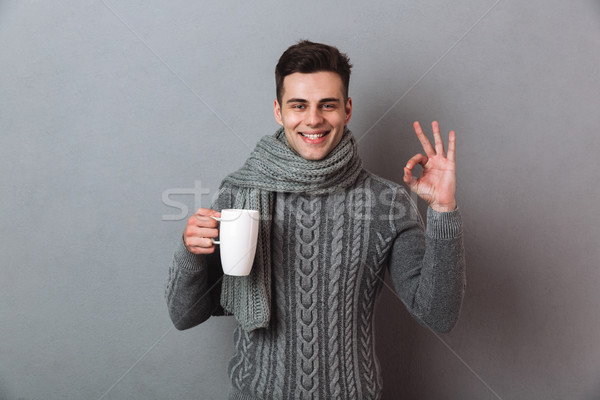 Happy man wearing warm scarf showing okay gesture. Stock photo © deandrobot