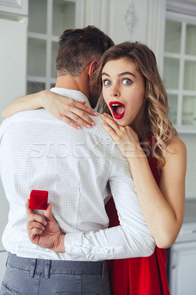 Amazed woman looking at box with engagement ring in her husband hands Stock photo © deandrobot