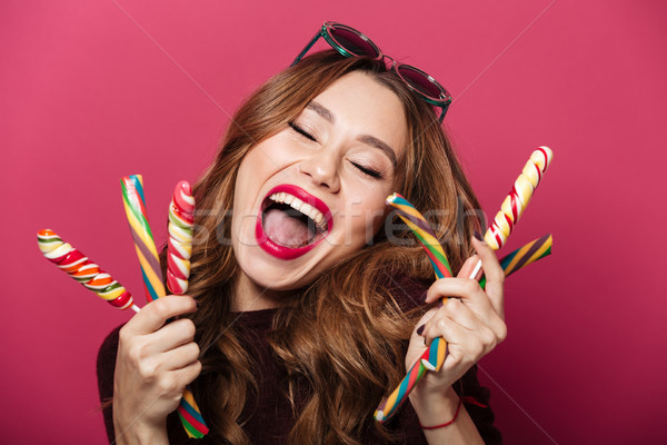 Amazing woman wearing glasses eating sweeties. Stock photo © deandrobot