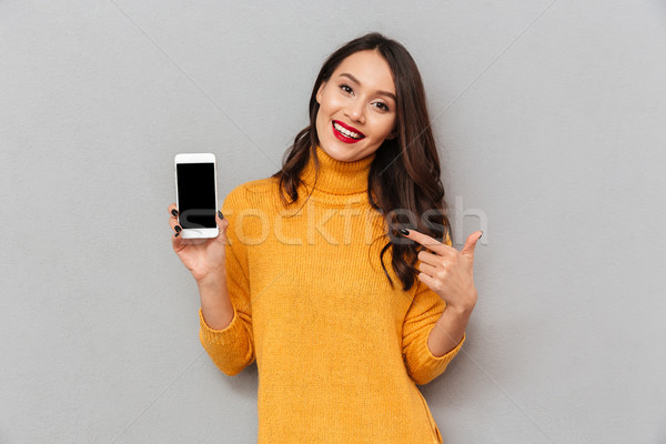 Mosolyog barna hajú nő pulóver mutat okostelefon Stock fotó © deandrobot