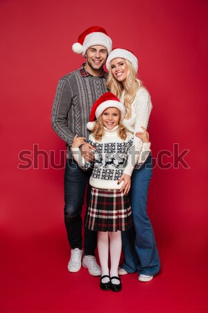 Happy punk couple in christmas hats looking at the camera Stock photo © deandrobot