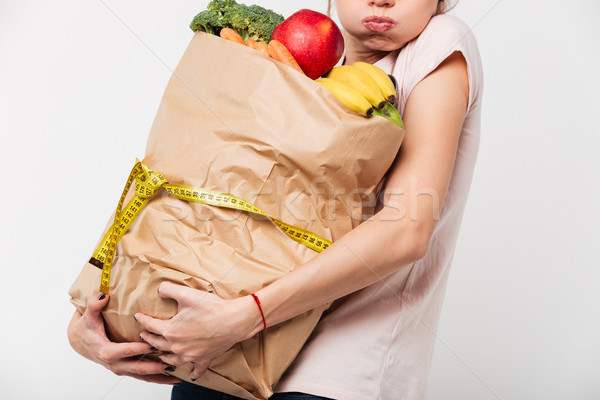 Close up of a woman holding heavy bag with groceries Stock photo © deandrobot