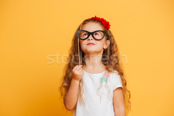Funny little girl child holding fake glasses looking aside. Stock photo © deandrobot