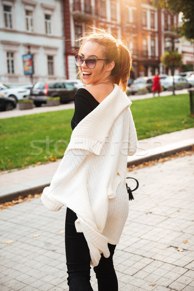 Cheerful pretty woman walking outdoors. Stock photo © deandrobot