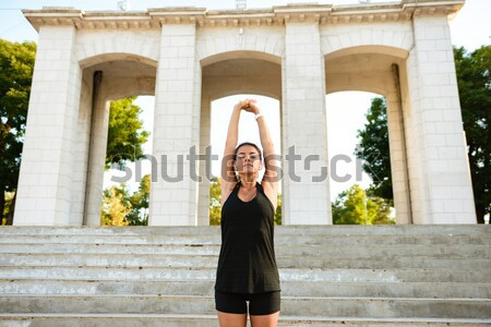 Portrait of a cheery fitness girl in earphones stretching Stock photo © deandrobot