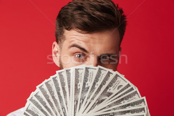 Man isolated over red wall holding money covering face. Stock photo © deandrobot