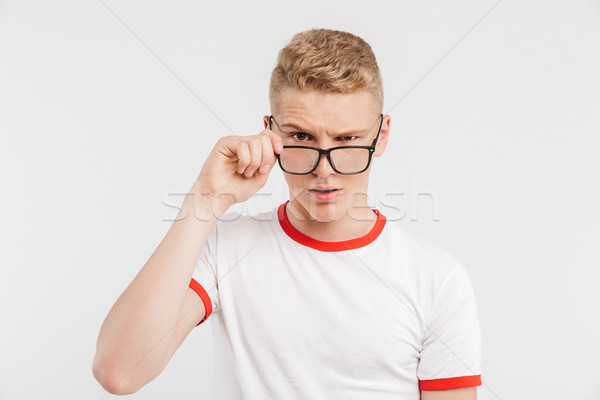 Portrait of a suspicious teenage boy in eyeglasses Stock photo © deandrobot