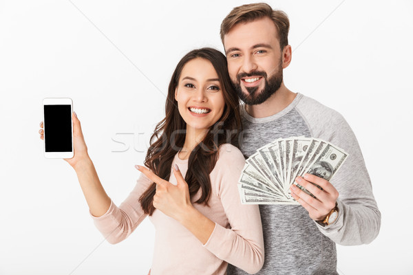 Happy young loving couple holding money showing display of mobile phone Stock photo © deandrobot