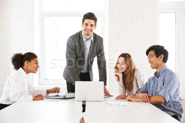 Happy young man chief standing at the table Stock photo © deandrobot