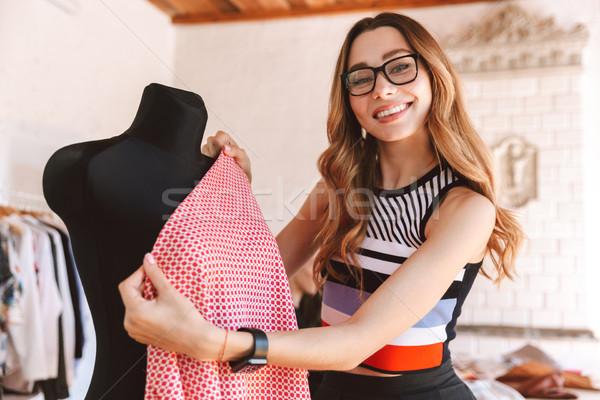 Mosolyog fiatal nő ruházat designer stúdió dolgozik Stock fotó © deandrobot