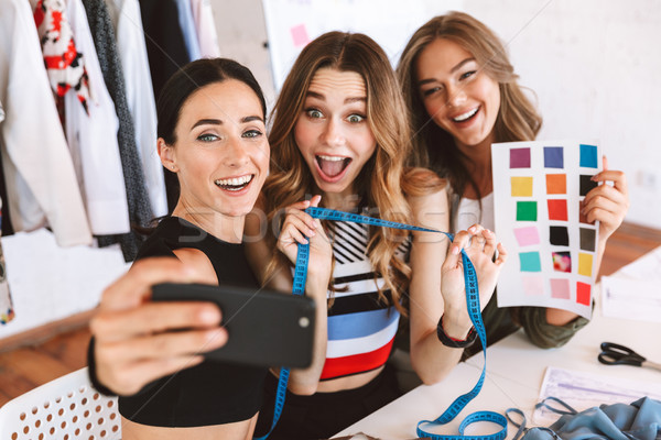 Three excited young women clothes designers Stock photo © deandrobot