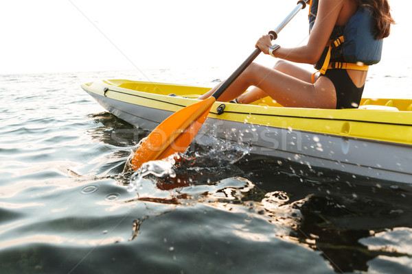Young woman kayaking on lake sea in boat. Stock photo © deandrobot
