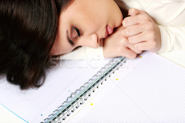 Young tired student fallen asleep at the table Stock photo © deandrobot