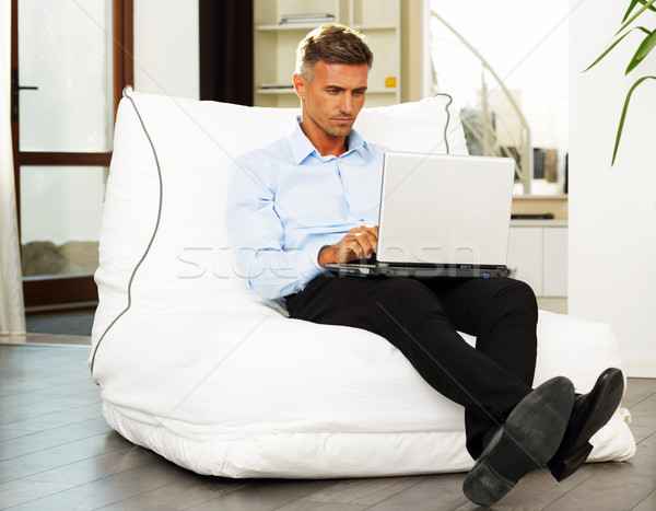 Goodlooking mature man relaxing at home in armchair with laptop Stock photo © deandrobot