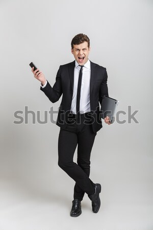 Full-length portrait of a businessman buttoning cuff sleeves on gray background Stock photo © deandrobot