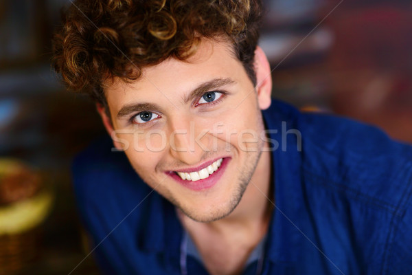 Closeup portrait of a young smiling man with curly hair Stock photo © deandrobot