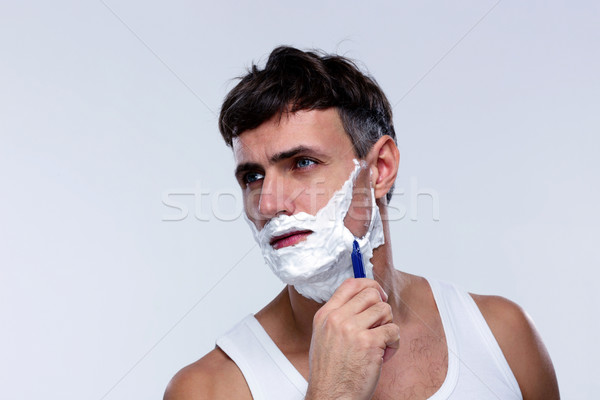 Handsome man shaving over gray background Stock photo © deandrobot