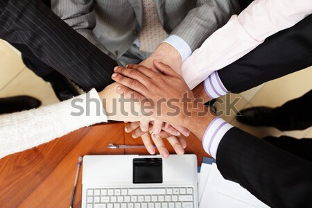 Image of business people hands on top of each other. View from above Stock photo © deandrobot