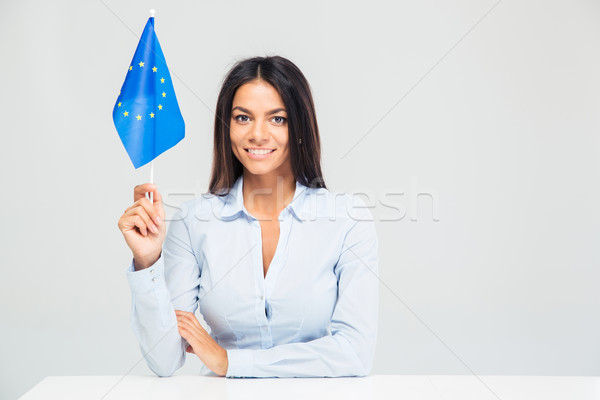 Businesswoman sitting at the table with european flag Stock photo © deandrobot