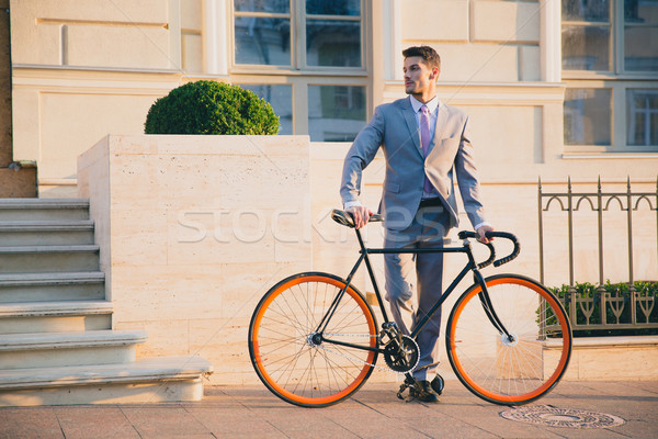 Stock photo: Portrait of a handsome businessman with bicycle