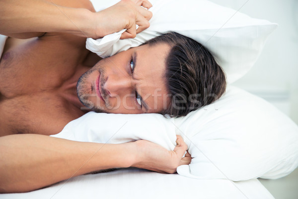 Man lying in the bed with pillow on head Stock photo © deandrobot