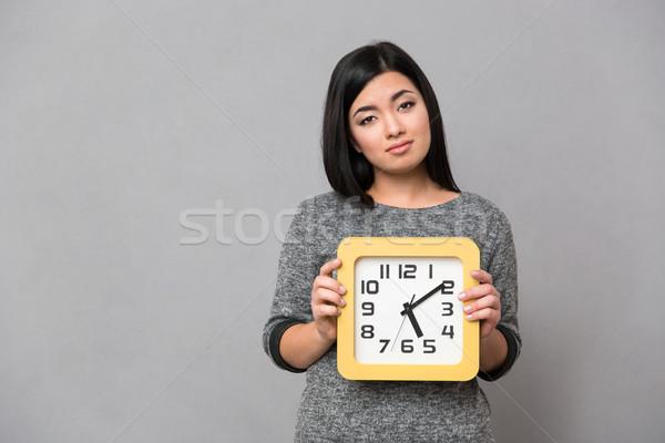 Portrait of a sad woman holding wall clock Stock photo © deandrobot