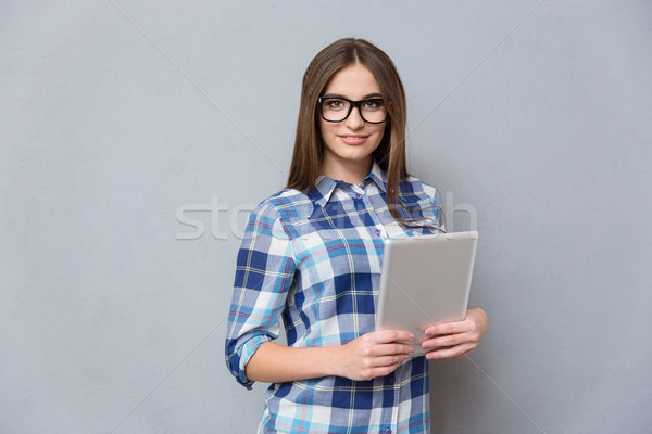 Pretty young woman in glasses holding tablet Stock photo © deandrobot