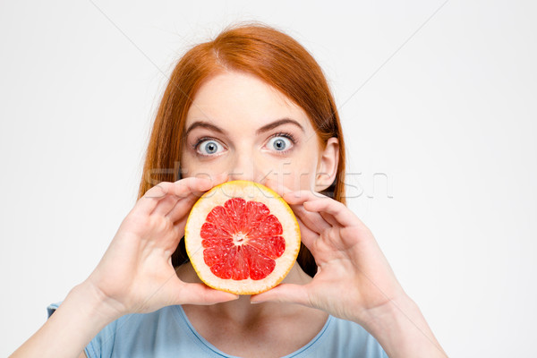 Shocked amusing lady holding grapefruit half in front of mouth  Stock photo © deandrobot