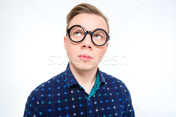 Funny thoughtful male in round glasses looking up and thinking Stock photo © deandrobot