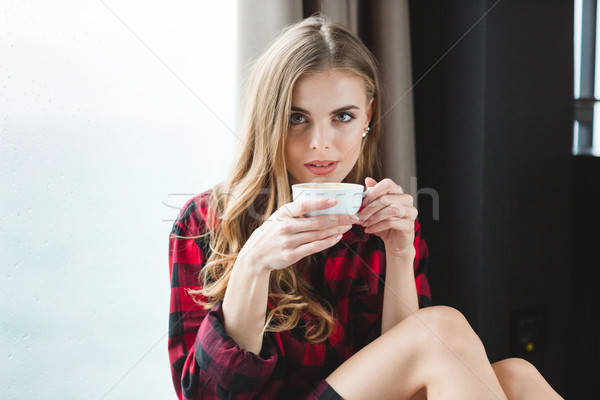 Beautiful thoughtful young woman in plaid shirt drinking coffee  Stock photo © deandrobot