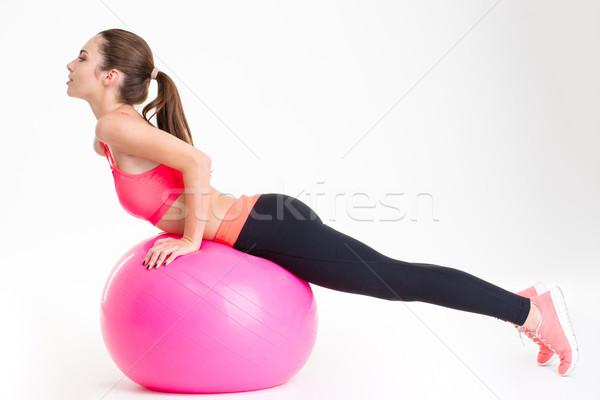 Fókuszált vonzó fiatal sportoló nyújtás rózsaszín Stock fotó © deandrobot