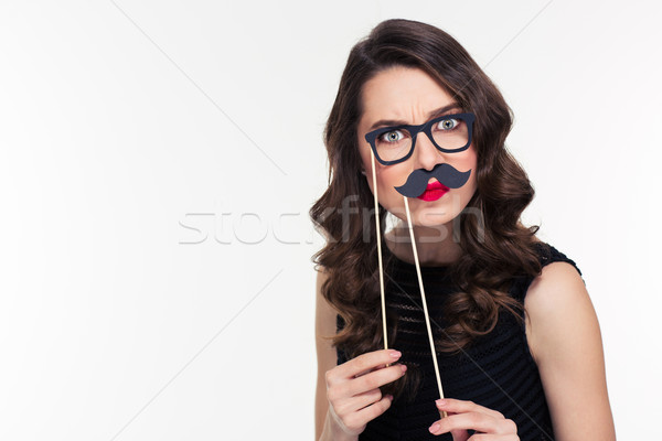 Comical curly young female playing with glasses and moustache booth  Stock photo © deandrobot