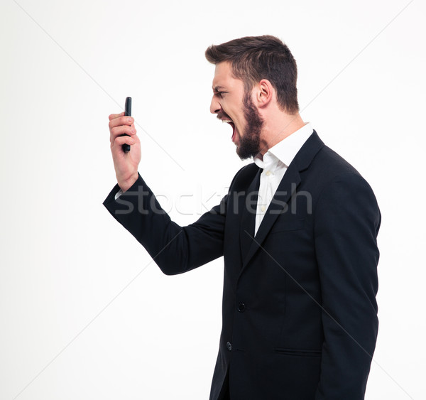 Angry businessman screaming on smartphone Stock photo © deandrobot
