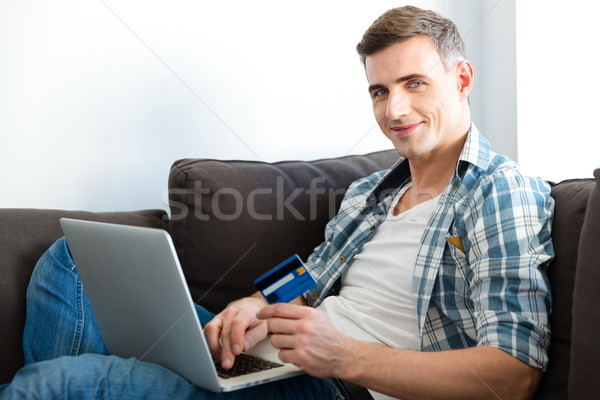 Happy man using laptop and making purchases with credit card  Stock photo © deandrobot