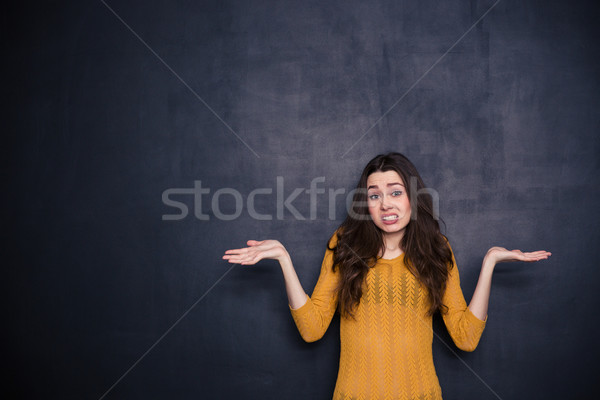 Young woman shrugging shoulders  Stock photo © deandrobot