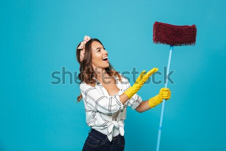 Happy housewife in blue apron wearing yellow gloves  Stock photo © deandrobot