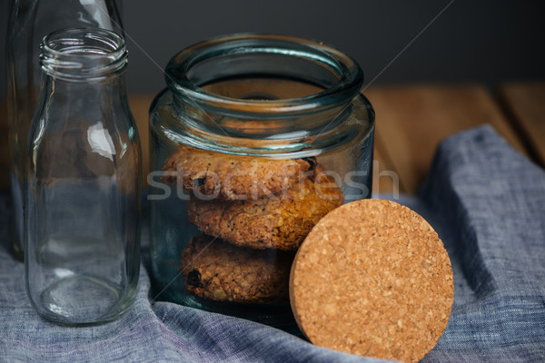 Oatmeal cookies in jar and empty glass bottles Stock photo © deandrobot
