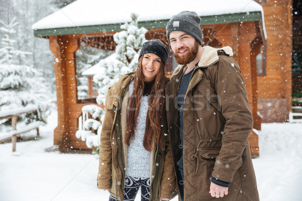 Couple standing near wooden cottage in winter Stock photo © deandrobot
