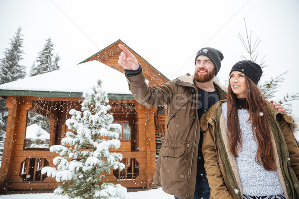 Man stading with girlfriend near log cabin and pointing away  Stock photo © deandrobot