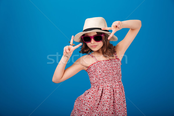 Cute playful little girl in hat showing victory sign  Stock photo © deandrobot