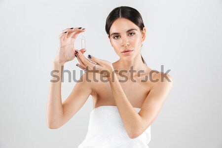 Pretty young woman holding bottle of parfume Stock photo © deandrobot